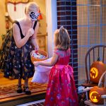 Costumed homeowner offers candy to child trick-or-treater