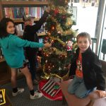three children gathered around a chritmas tree