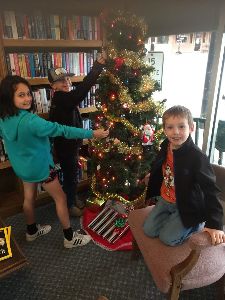 three children around a christmas tree