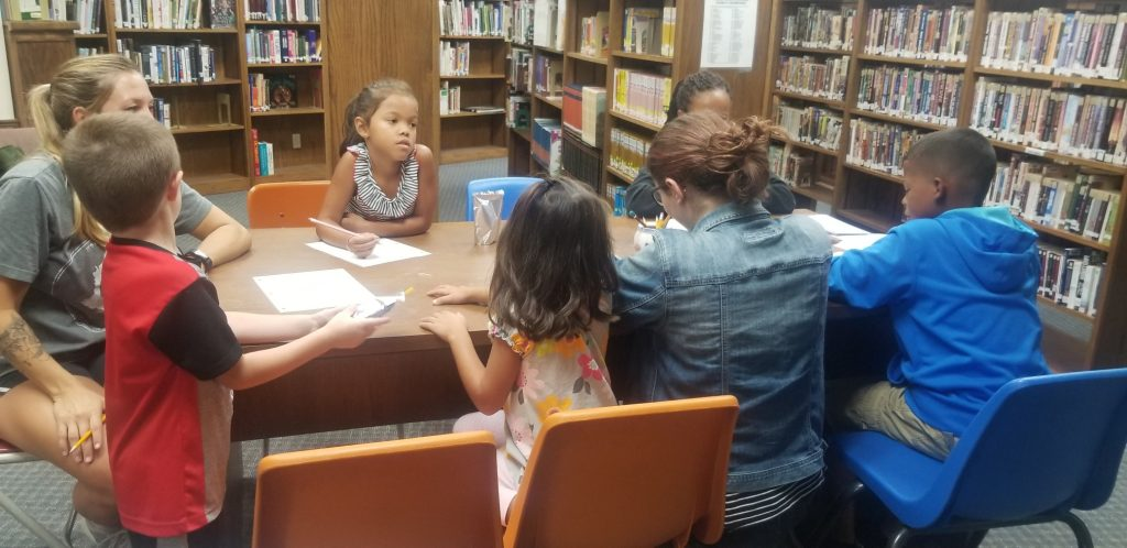 children sitting at a library table writing on paper