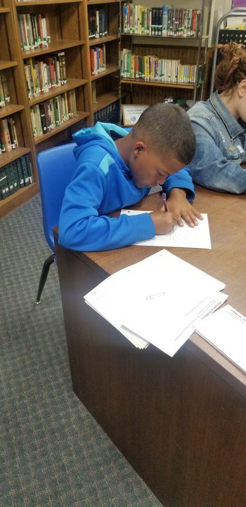 boy writing at a table