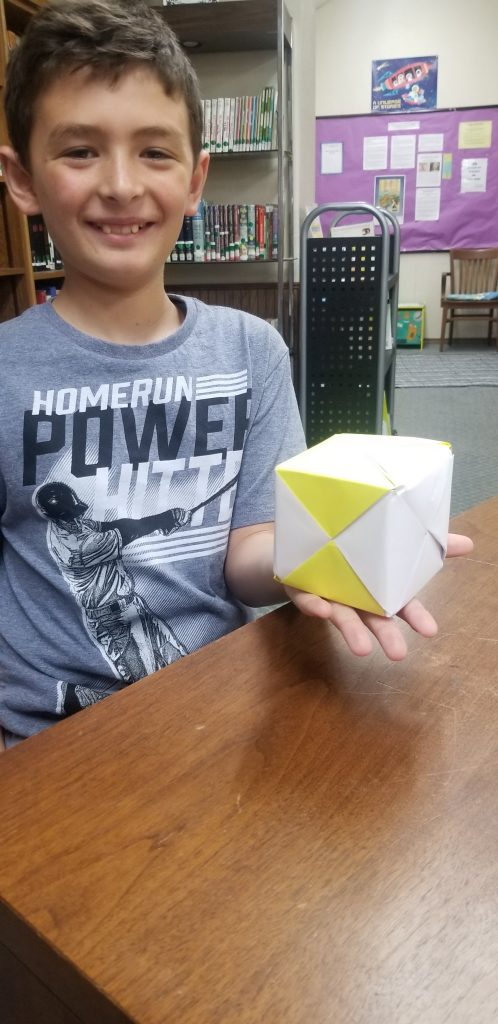 boy holds a sonobe cube which is a modular origami piece