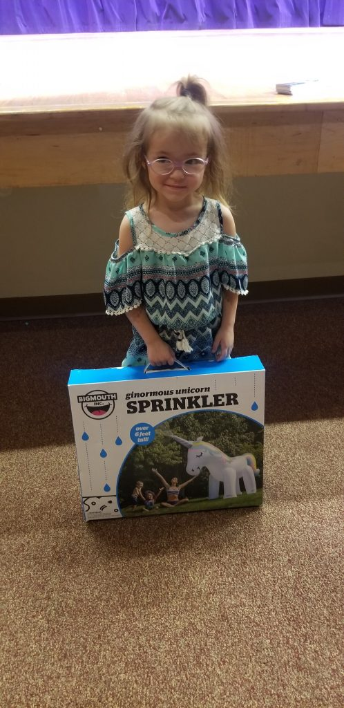 little girl with glasses hold a unicorn sprinkler box and poses for picture