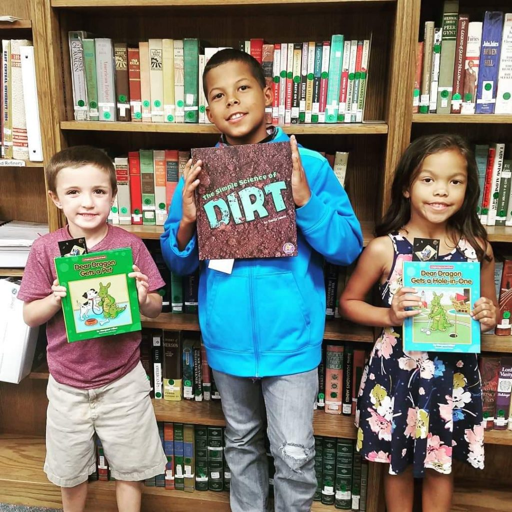 three children each hold up their own book and pose for a picture