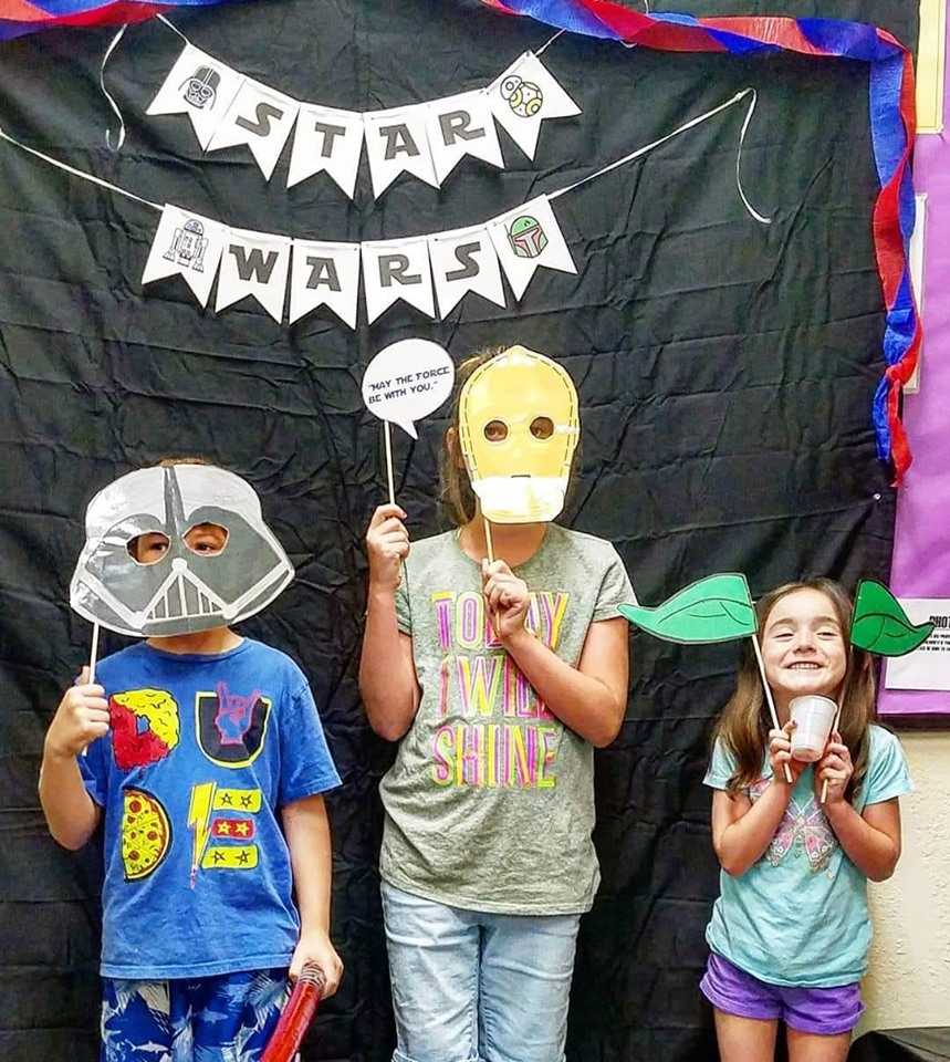 three children taking pictures at a star wars photo booth. The boy is holding a darth vader mask, the middle girl is holding a C3PO mask, and the youngest girl is holding yoda ears to her head and smiling.