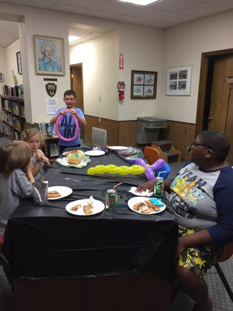 children eating pizza and making balloon animals in the library.