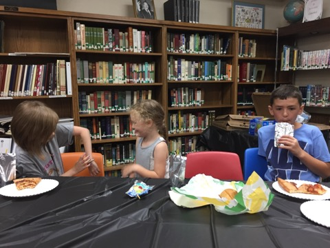 Three kids eating pizza in a library.