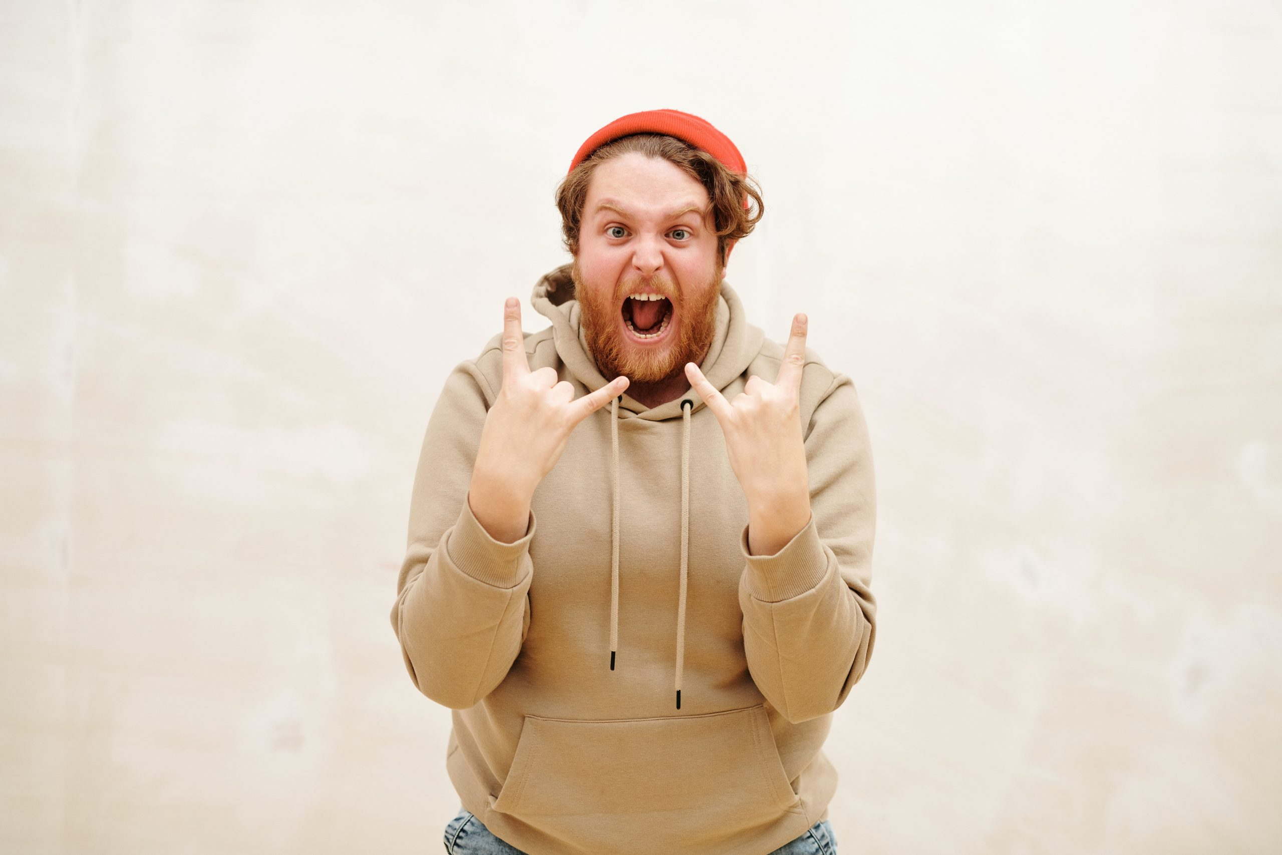 """man in beige hoodie and orange beanie gives double """"rock on"""" hand singles, seemingly in excitement"""